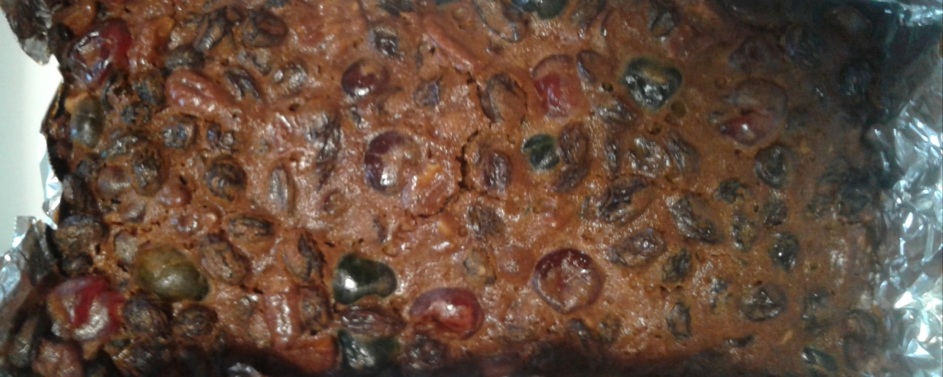 Freshly baked Christmas fruitcake in foil